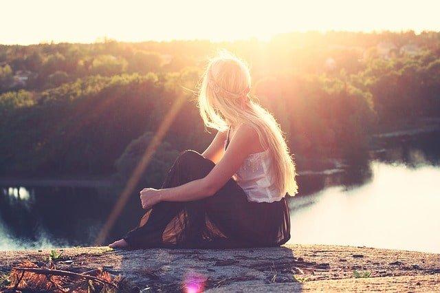Gewohnheiten - Frau sitzt auf Felsen und schaut in die Sonne
