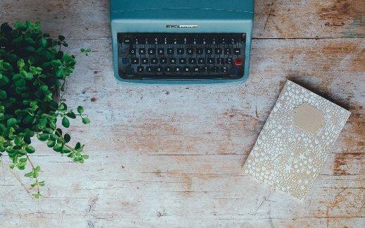 Schreiben gegen Unzufriedenheit - Schreibmaschine, Notebook, Pflanze