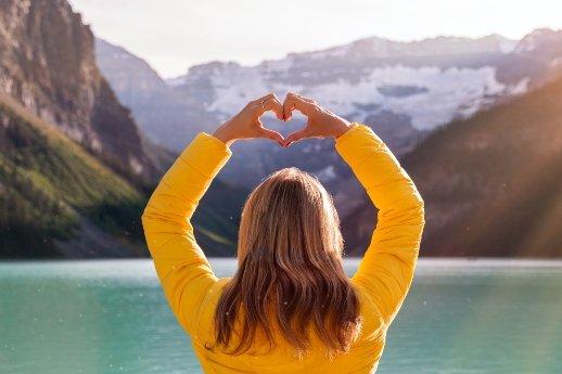 Frau, Rückenansicht, hält Arme nach oben und macht mit den Händen eine Herzform. gelbe Jacke, Seeblick